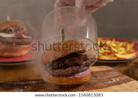 Close-up of chef's hand lifting a glass bowl of delicious homemade smoked hunger with wood chips from Jack Daniel's, shredded BBQ pork and American salad base steaming on wooden cutting board.