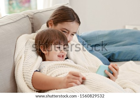 Happy siblings snuggling in warm knitted blanket at home on sofa watching cartoon laughing. Sister and brother having fun together. Autumn lifestyle, leisure activity