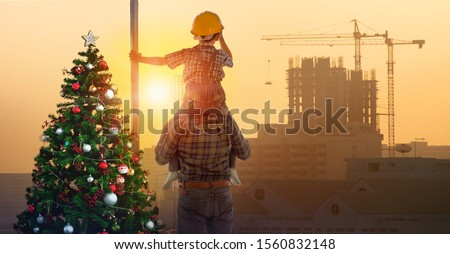 Asian boy on father's shoulders near Christmas tree with background of new high buildings and silhouette construction cranes of evening sunset, Christmas time between father and son