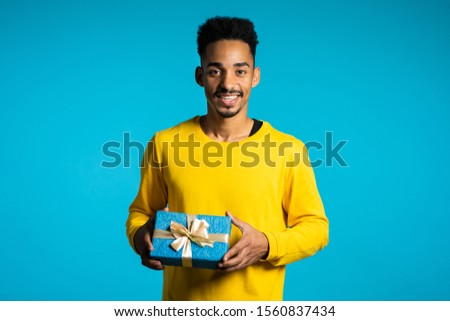 Handsome man in yellow wear holding gift box on blue studio background smiles to camera. Happy african american birthday guy.