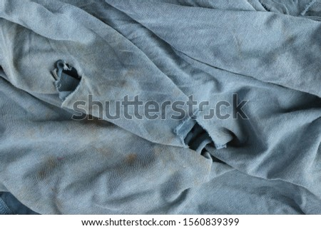 Old dirty ragged cloth texture. Blue gray fabric with brown spots and holes. Crumpled torn rag. Grunge background.  #1560839399