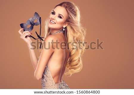 Beautiful young blonde woman in sexy glitter costume holding a mask. Party carnival glamour photo #1560864800