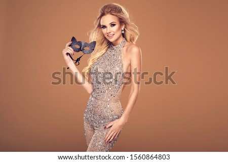 Beautiful young blonde woman in sexy glitter costume holding a mask. Party carnival glamour photo #1560864803