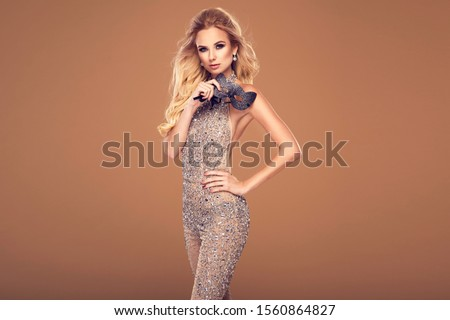 Beautiful young blonde woman in sexy glitter costume holding a mask. Party carnival glamour photo #1560864827