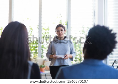 Student presenting project in training room. Young woman in casual holding notebook and speaking before audience. Presentation concept #1560870107