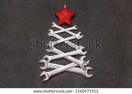Christmas tree made of tools. Wrenches spanners on black background. Industrial greeting card and happy new year creative concept. #1560971912