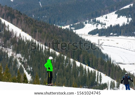Skiers descend on the slopes of the Carpathian slopes and mountains, on the background are picturesque scenery and ski slopes. #1561024745