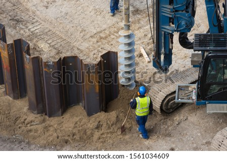 installing sheet piling on construction site with drilling rig Royalty-Free Stock Photo #1561034609