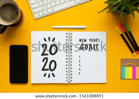 Stock photo of 2020 new year notebook with list of goals and objects on yellow background #1561088891
