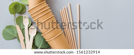eco natural paper cups, straws, wooden cutlery flat lay on gray background. sustainable lifestyle concept. zero waste, plastic free items. stop plastic pollution. Top view, overhead, template, Mockup. Royalty-Free Stock Photo #1561232914