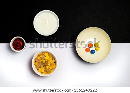 Group of  ceramic bowls filled with milk, cereal and dry goji berries for a healthy  breakfast on a white and black background #1561249222