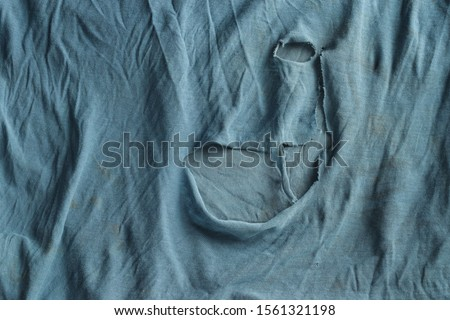 Grunge cloth for background. Texture of an old dirty ragged t shirt. Blue gray fabric with brown spots and holes. Crumpled torn rag #1561321198