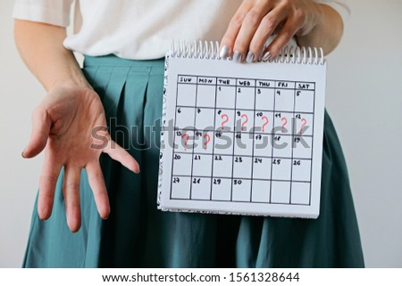 Missed period and marking on calendar. Unwanted pregnancy, woman's health and delay in menstruation. Period late Royalty-Free Stock Photo #1561328644