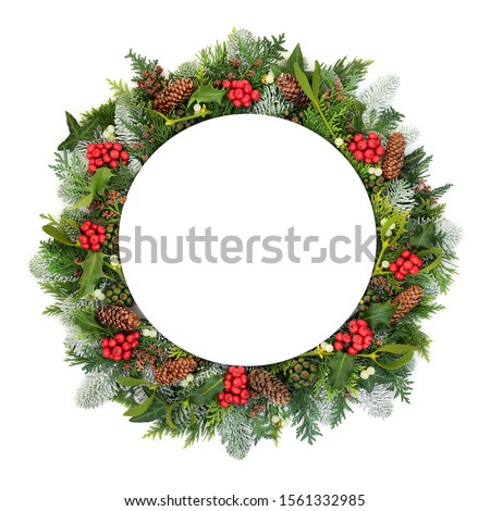 Christmas & New Year table setting with round porcelain plate with natural winter holly, snow covered fir, mistletoe, ivy, cedar leaves & pine cones on white background. Festive theme.