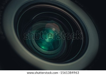 Beautiful camera lens with geen and pink light of glass on a black background. Macro photography view.