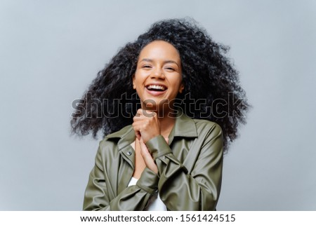 Overjoyed dark skinned curly woman laughs happily, laughs at funny joke, keeps hands pressed together, dressed in fashionable clothes, isolated over grey background. People and positiveness. #1561424515