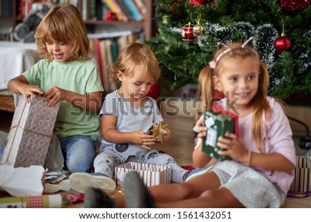 Happy  childhood on  Christmas.Smiling Kids opening Xmas presents.