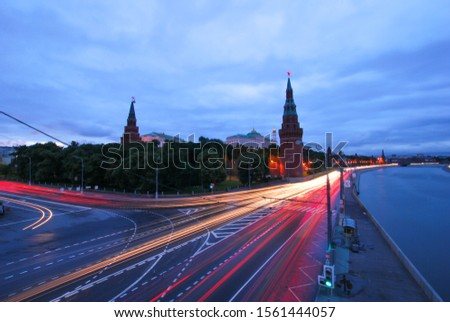 Night Moscow, Kremlin, pavement, photographed with a long shutter speed, cars driving in the foreground left tracks of lanterns and stars burn on spiers