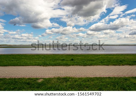 the expanse of the lake and the sky with clouds merge into one beautiful picture