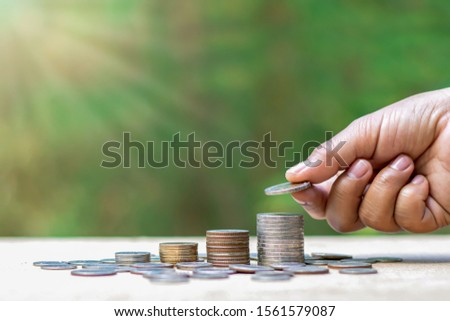 The hands of investors holding coins and coin piles at different levels from financial concepts, saving money and investing. #1561579087