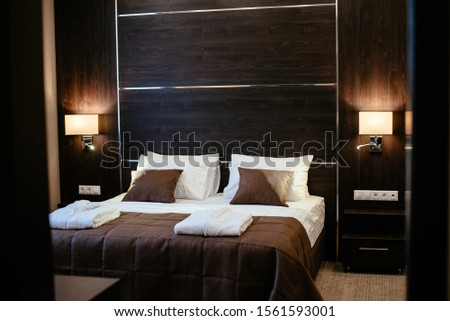 A cozy hotel room in a pastel-brown. Close Up of a large bed with a wooden headboard and beautiful bedding, with pillows and a blanket in brown, white in the modern bedroom interior. Film noise #1561593001