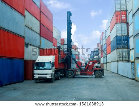 Container stacker, load the container into the truck. Work in the cargo port #1561638913