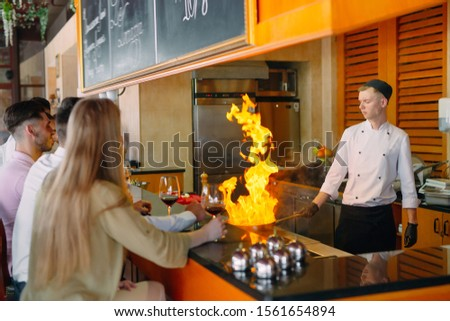The chef prepares food in front of the visitors in the restaurant.