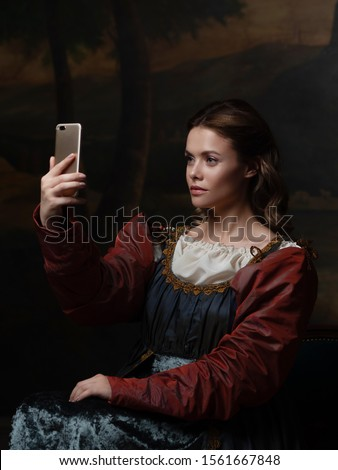 Old and new, concept. Beautiful young Renaissance style woman taking selfie on phone. Beautiful mysterious girl in the style of a Renaissance painting. #1561667848