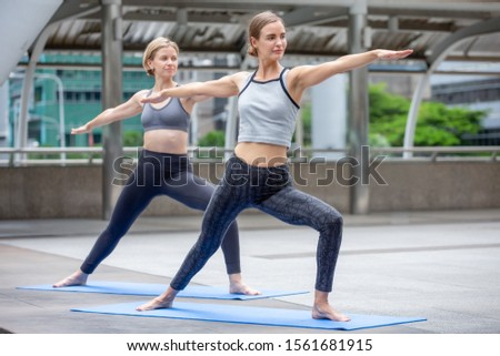 group of  beautiful young fitness women doing yoga stretching arm and leg in urban city outdoors . two friend sport girl exercise together . workout healthy lifestyle. City life concept . slender #1561681915