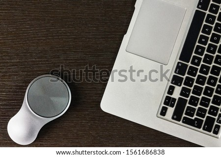 laptop and stylish mouse on table Royalty-Free Stock Photo #1561686838