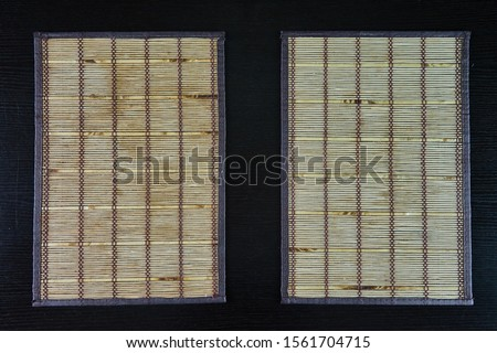 two bamboo mats on wooden table Royalty-Free Stock Photo #1561704715