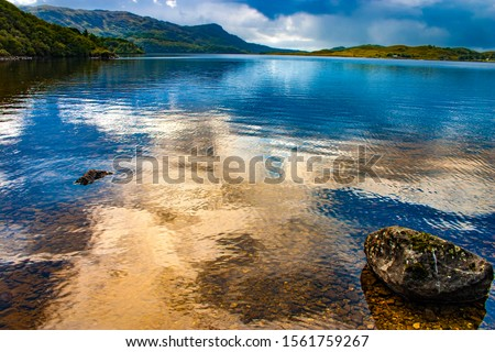 Photo of a landscape, lake, reflections of the cloudy sky in the hightlands in Scotland