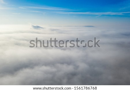 Aerial photo above the fog or white clouds with shining sun. Beautiful sunrise cloudy sky from aerial view. Above clouds from airplane window or drone. #1561786768
