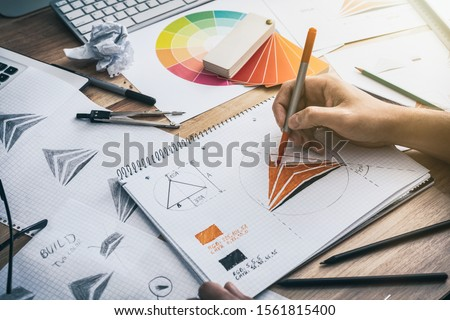 Graphic designer drawing sketches logo design. The concept of a new brand. Professional creative occupation with idea. Royalty-Free Stock Photo #1561815400