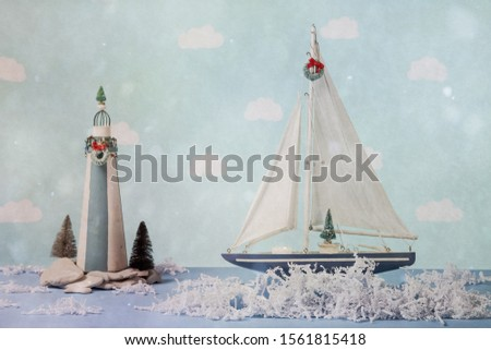 Sailboat and lighthouse with shredded paper water in a Christmas scene