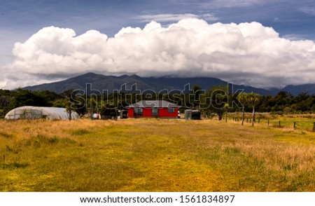 small farm with modern, red house in front of magnificent mounta #1561834897