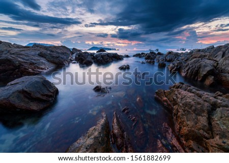 Long exposure image of Dramatic sky seascape with rock in sunset scenery background.