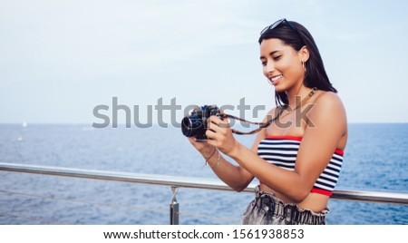 Attractive millennial tourist checking photo images on modern technology standing near ocean during summer vacations, beautiful Hispanic hipster girl editing pictures on advanced SLR camera