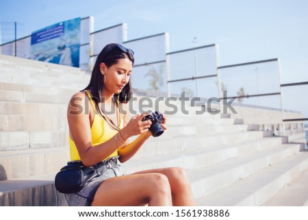 Skilled female amateur photographer checking photos on SLR camera spending time for images hobby, Latin hipster girl resting on urban setting and editing pictures on modern technology for professional