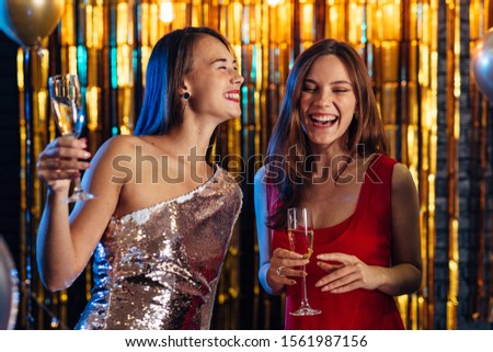 Two girls laughing while holding glasses of champagne, friends celebrating New Year, Christmas #1561987156