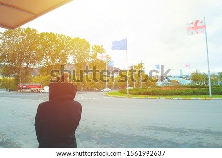 Girl in black winter suit standing on bus station with Georgia and European flag in background on traffic transportation #1561992637