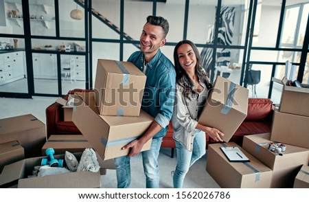 A young married couple in the living room in the house unpack boxes with things. Happy husband and wife are having fun, are looking forward to a new home. Moving, buying a house, apartment concept. #1562026786