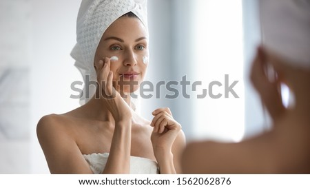 Attractive young adult woman apply facial cream look in mirror, beautiful healthy lady wrapped in towels put moisturizing lifting nourishing day creme on soft hydrated moisturized skin in bathroom #1562062876