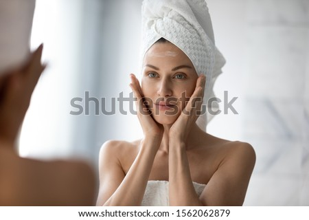 Beautiful young woman look in mirror massaging face applying cream in bathroom, pretty lady wrap towel on head put facial moisturizer lifting hydrating moisturizing creme, skin care treatment concept #1562062879