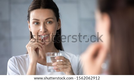Young healthy woman holding pill glass of water looking in mirror, adult lady take daily medicine diet vitamin omega supplements for beauty skin hair health care medicament stand in bathroom concept #1562062912