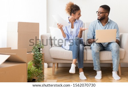 Buying Own House. Happy Afro Couple Using Laptop Reading Ownership Papers Sitting On Couch After Moving Apartment. Copy Space #1562070730
