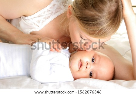 baby with his mother been cared for after having a good night sleep in bed at home with people stock photography stock photo