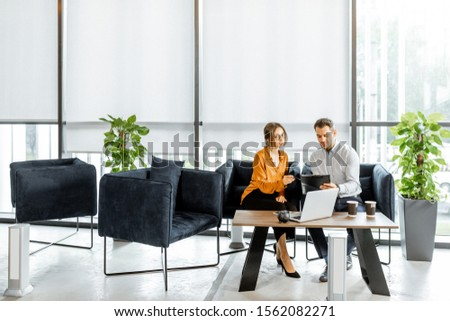 Young couple sitting on the comfortable sofa at the bank or financial institution office, solving some business or legal affairs. Wide view with big window and copy space Royalty-Free Stock Photo #1562082271