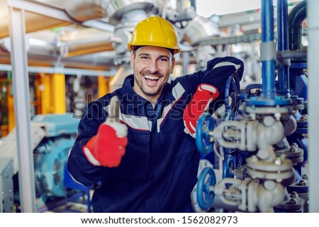 Smiling handsome caucasian worker in protective working clothes and with helmet on head leaning on boiler and giving thumbs up while standing in factory. Royalty-Free Stock Photo #1562082973