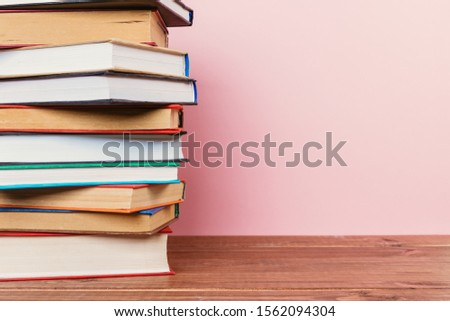 Simple Simple composition of many hardback books, unprocessed books on a wooden table and a pale pink background. back to school. Copy space Education. #1562094304